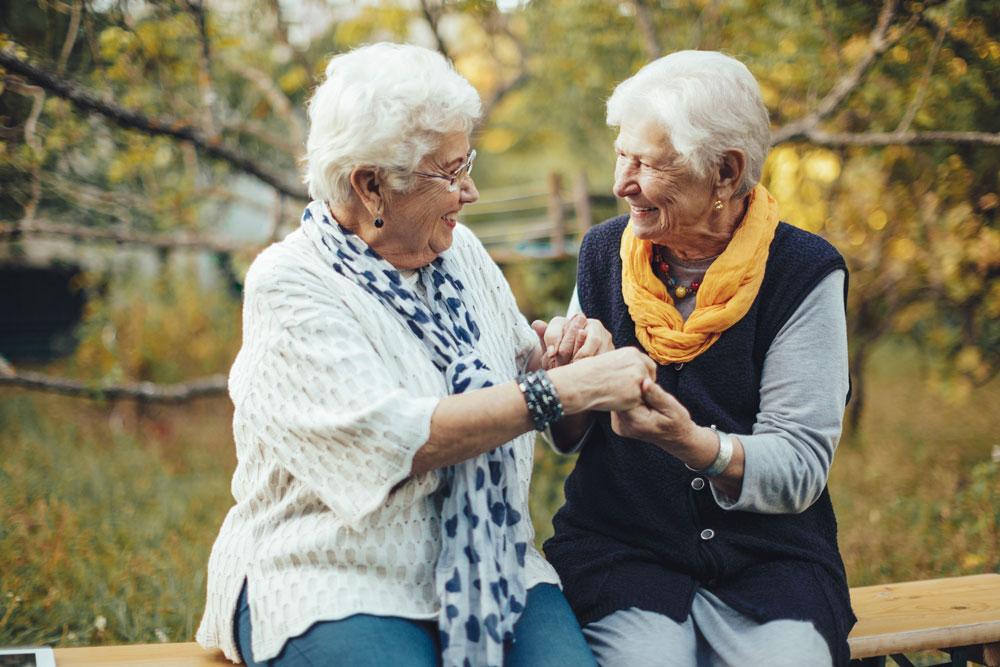 female senior living residents outside clasping hands